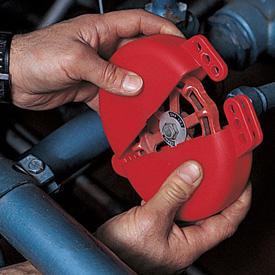 Twee handen die een vergrendeling plaatsen op de draaiknop van een industriële installatie