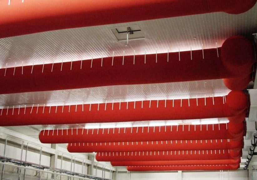 Een industrieel plafond met daaraan rode airsocks
