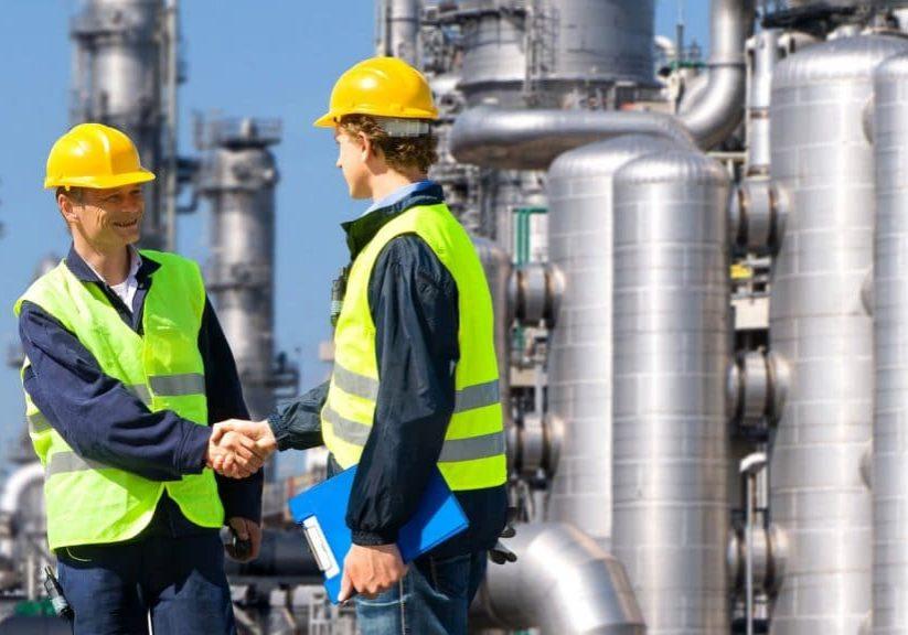 Twee mannen in veiligheidshesjes en met een bouwhelm die handen schudden voor een industriële installatie