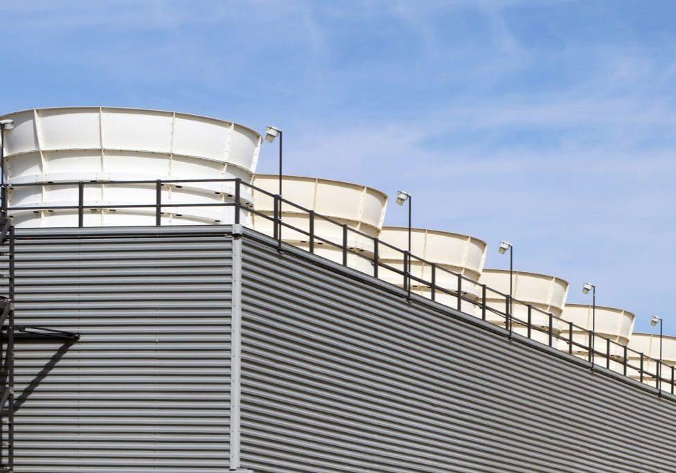 Het dak van een industrieel gebouw met daarop 6 witte koeltorens