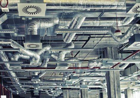 Luchtkanalen geplaatst aan een open plafond in een industriële ruimte