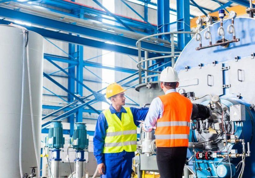 Twee mannen die het mechanisch onderhoud van een blauwe industriële ketel uitvoeren (vacatures)