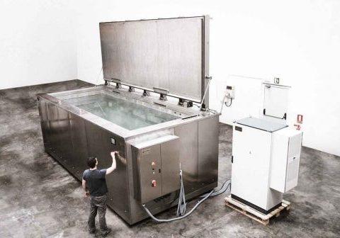 Een groot industrieel bad, bediend door een man die een ultrasone reiniging uitvoert