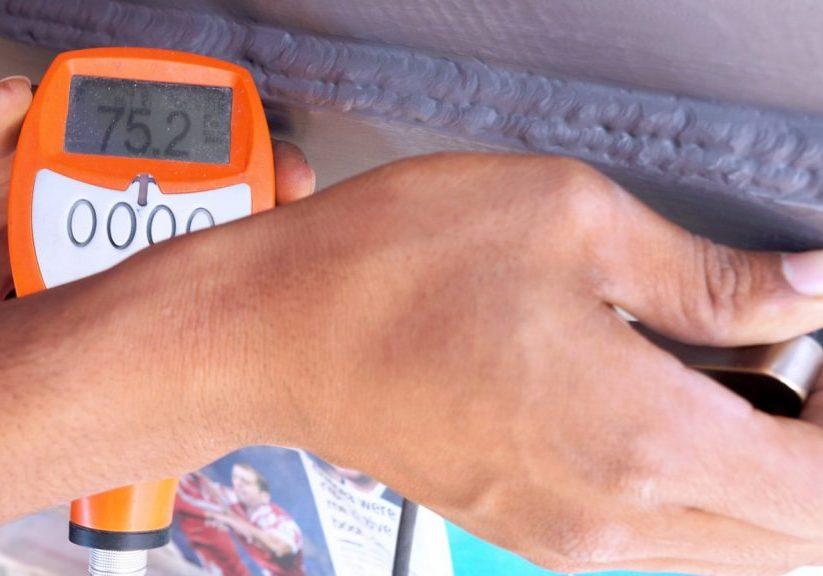 Een hand die met een oranje apparaat de dikte van een zinklaag opmeet